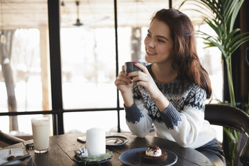 Woman snacking sweets and drinking coffee in a cafe