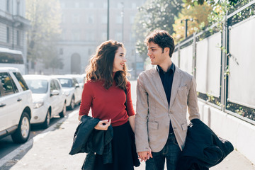 Young beautiful couple in love chatting walking outdoor in the city, having fun - first date,  romantic, love concept