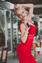 Portrait of beautiful woman singer in red dress at restaurant