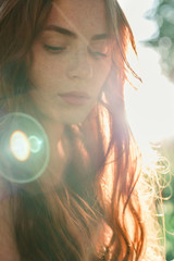 Foto auf AluDibond Buddha Beautiful redhead girl in sun rays