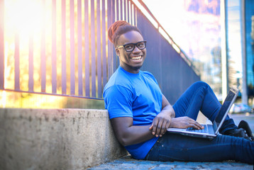 Black boy sitting by a fence with laptop