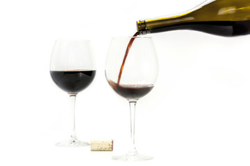 Red wine poured from bottle into glass, on white