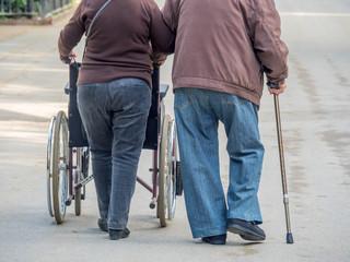 Mann mit Gehstock und Rollstuhl