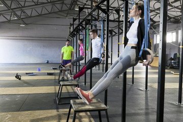 Athletes doing gym exercise on rings in gym