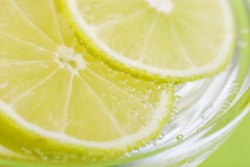 Slices of lemon in the glass with water close upю Lemonade drink.