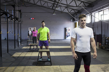 Athletes prepare for doing box jumps in gym