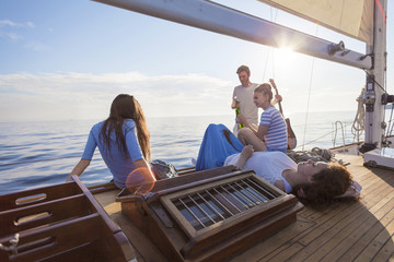 Friends relaxing on boat deck of sailboat