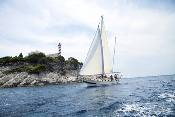 Sailing ship with lighthouse in background