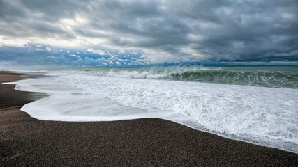 Winter sea waves hitting sand beach at stormy weather morning on Black sea shore of Abkhazia with dramatic leaden sky nature background