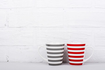 pair of ceramic mugs with the same striped pattern, but in different colors, gray and red against a white brick wall. The horizontal