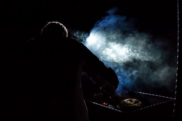 Silhouette of tourist making campfire in the night