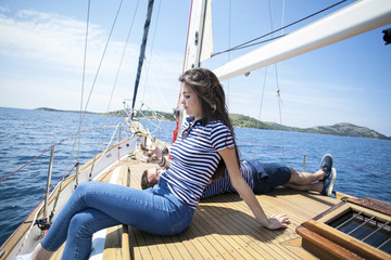 Young woman using smartphone on deck of sail ship