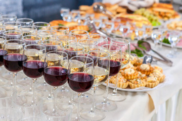 Alcoholic beverages in glasses and snacks on buffet table, catering