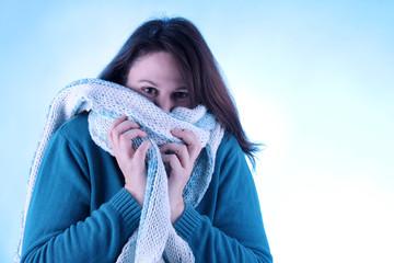 Frau schützt sich mit Schal vor Kälte