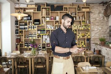 Male owner of oil bar using digital tablet at restaurant