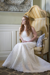 Bride sits on chair showing off wedding dress