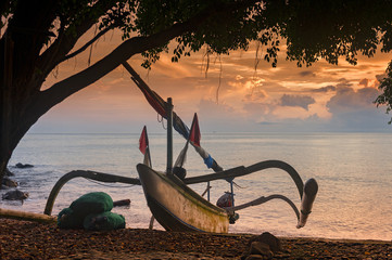 Balinese Traditional Outrigger Fishing Boat. A Balinese fishing boat, called a jukung, on the beach in the Amed area of eastern Bali during a glorious sunrise.