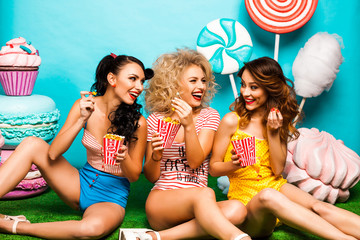 Three young cool lady, on a turquoise background surprised looking at the camera, eat popcorn, fashionable Pin-up girl, perfect make-up and hairstyles, bright Body, Hollywood, red lips, crazy emotions