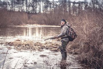 hunter man creeping in swamp during spring hunting season