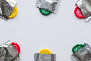 colored condoms on a white background. frame for text