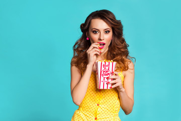 Amazing cute young pretty girl on the turquoise background eats popcorn and surprised looking at the camera, wearing a bright yellow body dresses, fashionable Pin-up girl, cool, smiling, hollywood