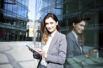 Portrait of businesswoman using digital tablet while standing