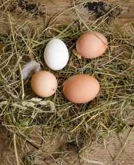 Fresh eggs are scattered in the hay. Wooden background. top view