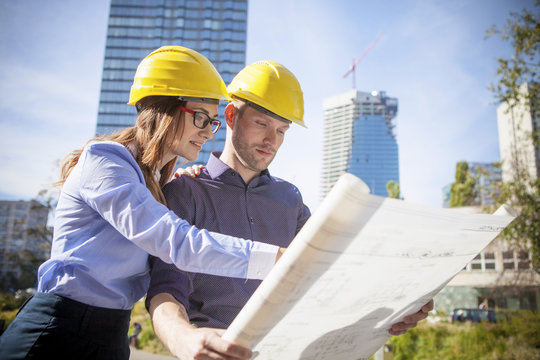 Two architects looking at a blueprint in city