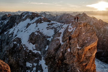 Two mountaineers standing on mountain peak in European Alps