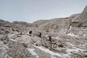 Group of mountaineers hiking on trail in mountain range