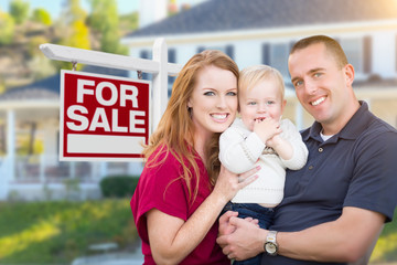 Happy Young Military Family in Front of For Sale Real Estate Sign and New House.