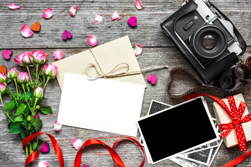 blank white greeting card with retro camera, blank photo, gift box and pink roses
