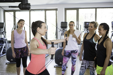 Fitness instructor shows women how to perform a suspension exercise