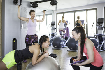 Woman working with fitness instructor in health club