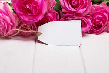 Beautiful pink roses and empty paper tag