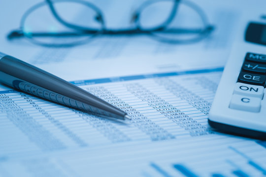 Finance, financial analysis, accounting accounts spreadsheet with pen glasses and calculator in blue. Close up concept for stock, bank accounting and book keeping data.