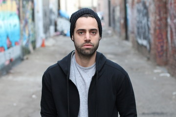 Portrait of young man against empty urban alley way - Stock image