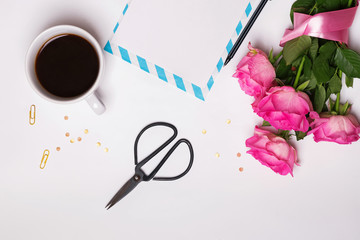 Bouquet of pink roses, coffee, blank paper  and other objects