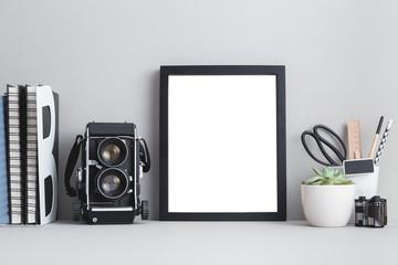 Photo frame and a camera on a shelf.