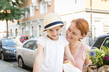 Portrait of mother with daughter in city