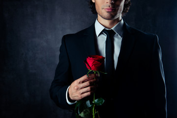 Close up of handsome young boyfriend holding red rose