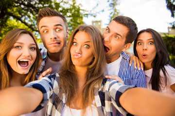five cheerful fooling best friends making selfie photo and havin