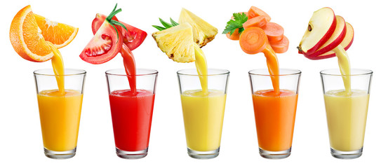 Fresh juice pours from fruit and vegetables into the glass isola