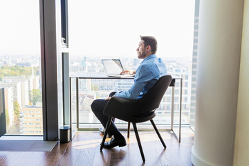 Businessman in apartment using laptop computer