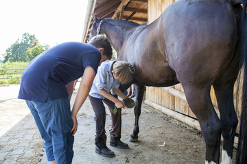 Boys cleaning hoof of a horse