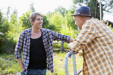Senior man and son by fence talking