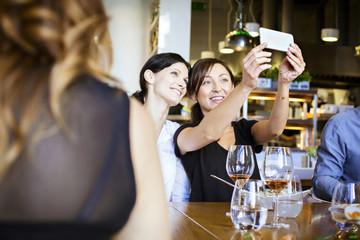 Two women taking a selfie in restaurant