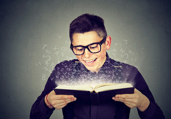 man reading a book with alphabet letters coming out