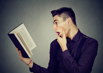 Amazed shocked man reading a book
