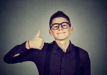 Successful teenager. Nerdy man giving thumbs up hand gesture sign